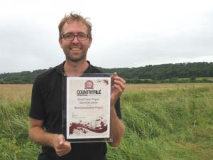 Damon holding the award